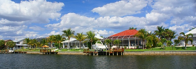 Picture showing finished homes at a Cape Coral canal from the back with installed boat docks