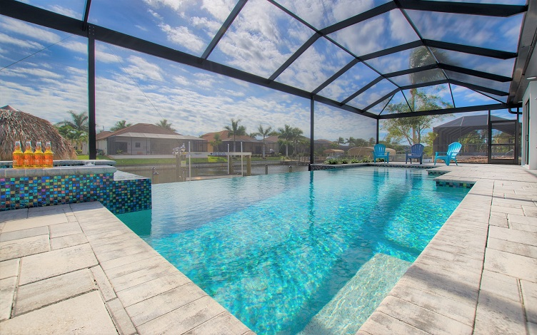Picture of the New Construction Model Royal Palm 2 viewing the oversize pool area with a blue water pool