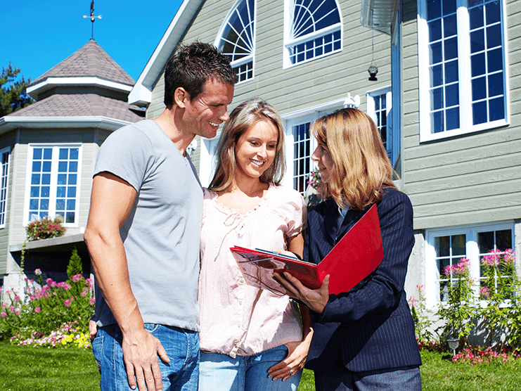 Picture of a Realtor showing information to clients in front of a house